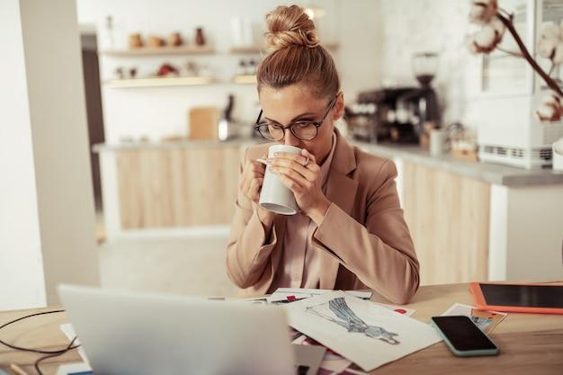 Opfleuren. geconcentreerde modeontwerper die naar de laptop kijkt en koffie drinkt terwijl ze op haar werkplek zit.
