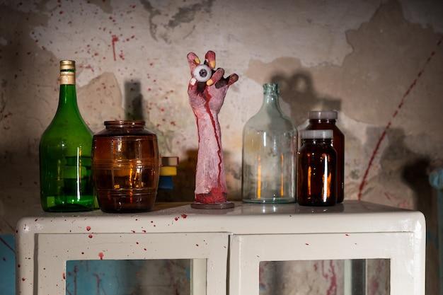 Opgedroogde geamputeerde hand met oogbol tussen glazen potten met bloedspattende muur