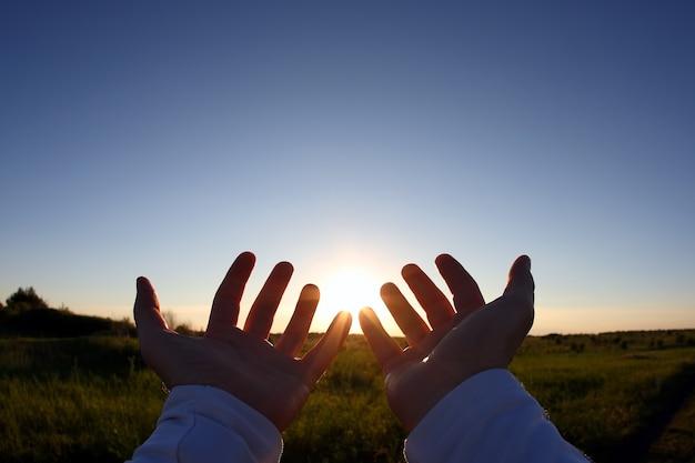 Opgeheven handen op de achtergrond van de zonsondergang