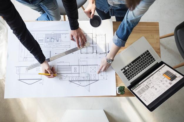 Opgeheven mening van architectenhand die aan blauwdruk over houten bureau op het werk werken