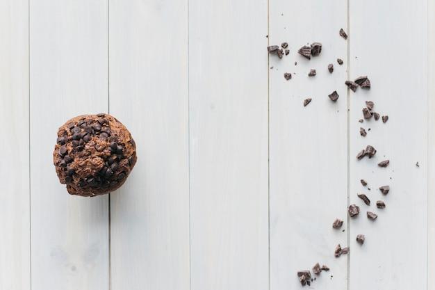 Opgeheven mening van choco-spaander cupcake en verspreide chocolade op houten achtergrond