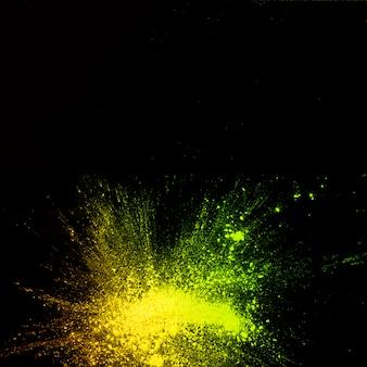 Opgeheven mening van de explosie van het gele kleurenpoeder op zwarte achtergrond