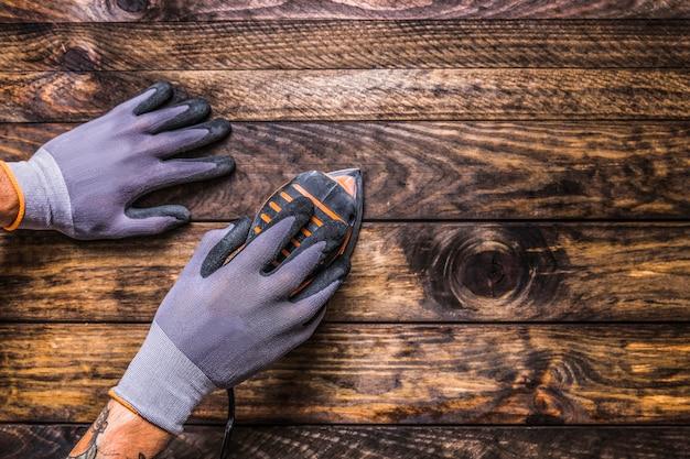 Opgeheven mening van de hand die van de timmerman schurende machine op houten achtergrond gebruikt
