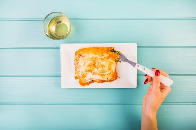 Opgeheven mening van de hand die van de vrouw lasagne op plaat eet