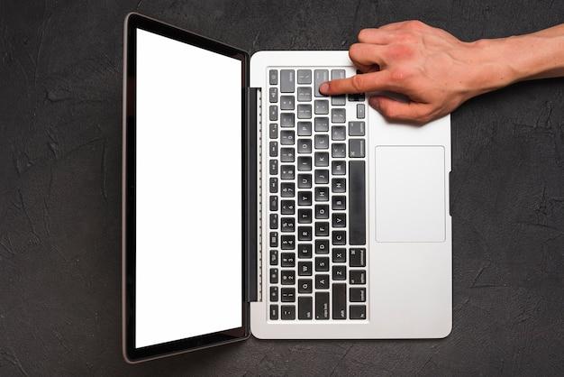 Opgeheven mening van de hand die van een persoon laptop op zwarte achtergrond met behulp van