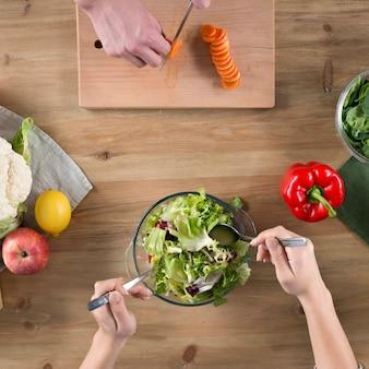 Opgeheven mening van de hand die van mensen voedsel over houten keukenteller voorbereiden