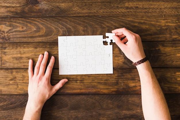 Opgeheven mening van de mens die puzzel over houten lijst oplost