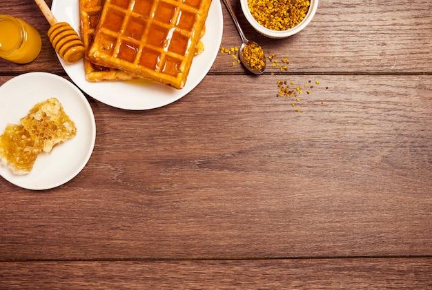 Opgeheven mening van de wafel van belgië met honing en bijenstuifmeel op houten geweven