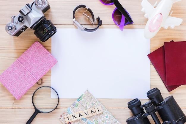 Opgeheven mening van divers reizend materiaal en een leeg witboek op houten achtergrond