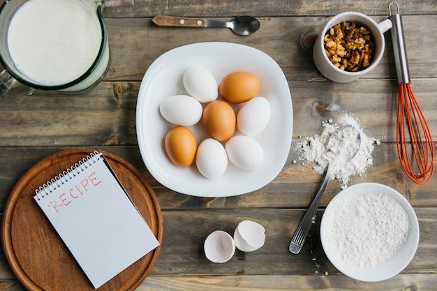 Opgeheven mening van diverse ingrediënten met spiraalvormige blocnote die receptenwoord tonen