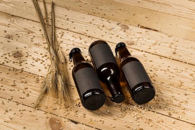 Opgeheven mening van drie bierflessen en oren van tarwe op houten achtergrond