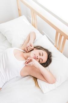 Opgeheven mening van een mooie vrouwenontwaken op bed bij ochtend