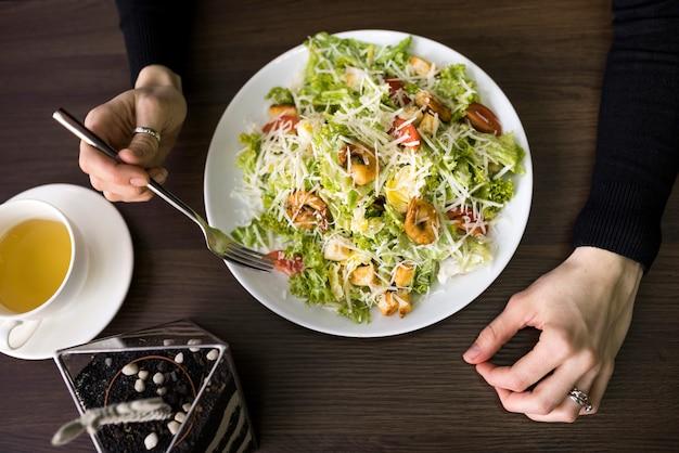 Opgeheven mening van een persoon die caesar salade met garnalen op witte plaat over lijst heeft