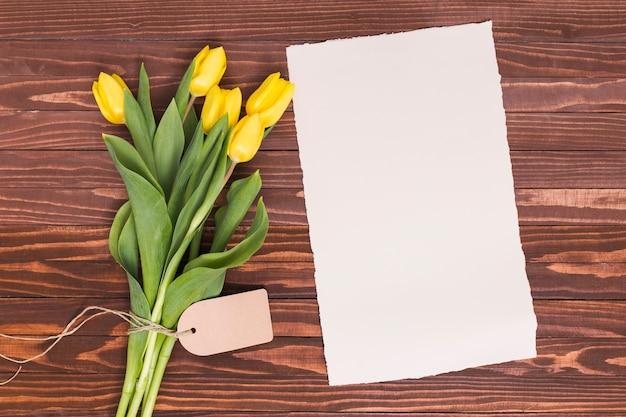 Opgeheven mening van gele tulpenbloemen met leeg document boven houten geweven achtergrond