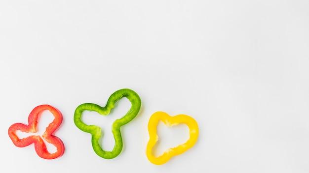 Opgeheven mening van gesneden kleurrijke groene paprika's op witte achtergrond