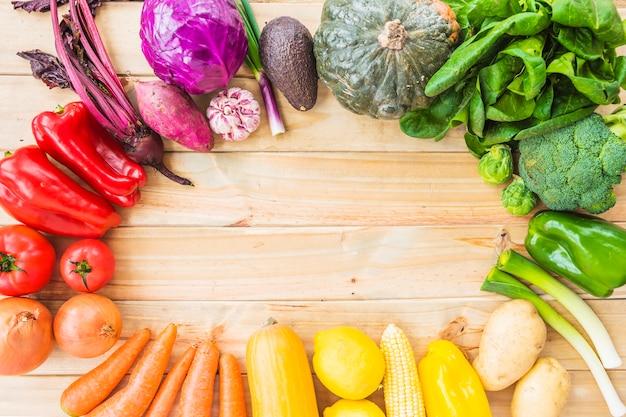 Opgeheven mening van gezonde groenten die cirkelkader op houten achtergrond vormen