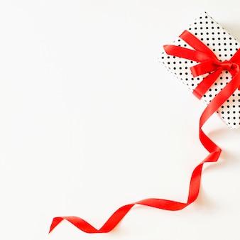 Opgeheven mening van gift die met rood lint op witte oppervlakte wordt gebonden