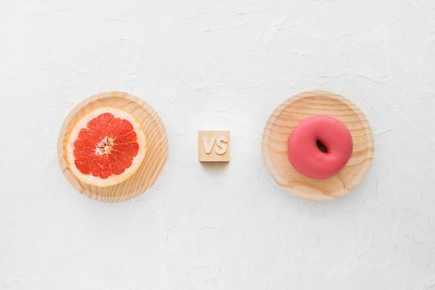 Opgeheven mening van grapefruit tegenover doughnut op witte achtergrond