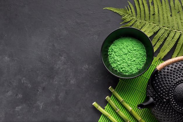Opgeheven mening van groen matchatheepoeder met varenbladeren en bamboestok op zwarte oppervlakte