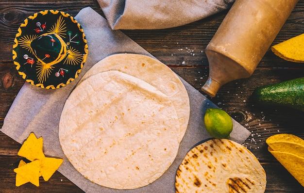 Opgeheven mening van heerlijke tarwe mexicaanse tortilla en smakelijke nachos op houten lijst met deegrol