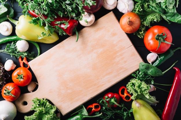 Opgeheven mening van houten die hakbord met verse groenten wordt omringd