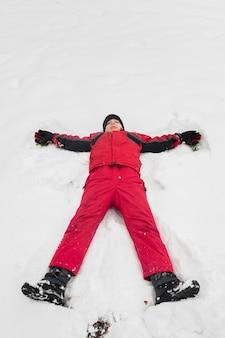 Opgeheven mening van jongen met de winterkleren die op witte sneeuw liggen