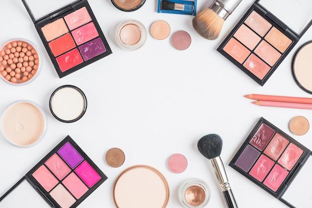 Opgeheven mening van kosmetische producten die kader op witte achtergrond vormen