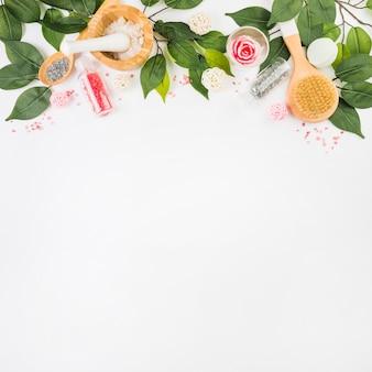 Opgeheven mening van kosmetische producten en groene bladeren bij de bovenkant van witte achtergrond