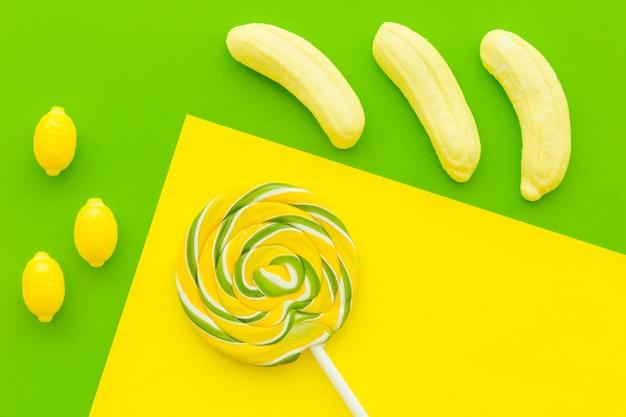 Opgeheven mening van lolly, banaan en citroencadies op multi gekleurde achtergrond