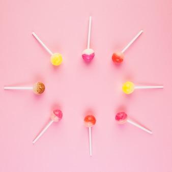 Opgeheven mening van lollys die kader op roze achtergrond vormen