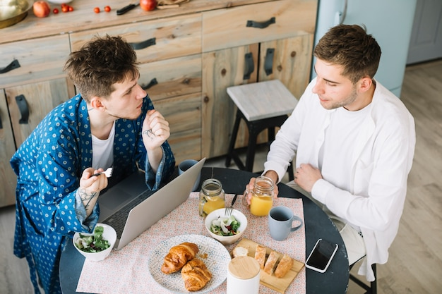 Opgeheven mening van mannelijke vrienden die ontbijt met sappen in keuken eten