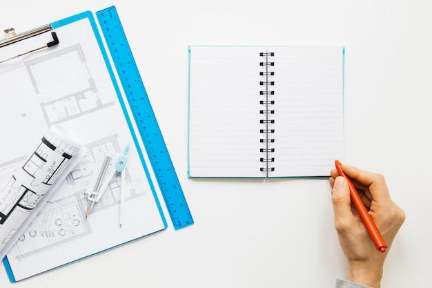 Opgeheven mening van menselijke hand die op agenda dichtbij blauwdrukklembord schrijven