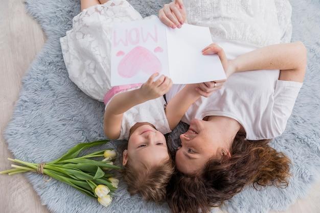 Opgeheven mening van moeder en dochter die op blauw pluizig tapijt met bloemen en groetkaart liggen