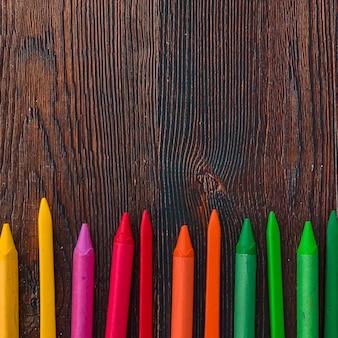 Opgeheven mening van multicolored waskleurpotloden op bruine plank