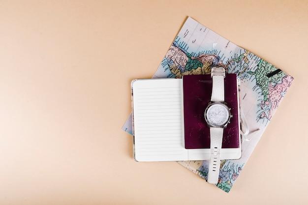 Opgeheven mening van polshorloge, paspoort, blocnote en kaart op beige achtergrond