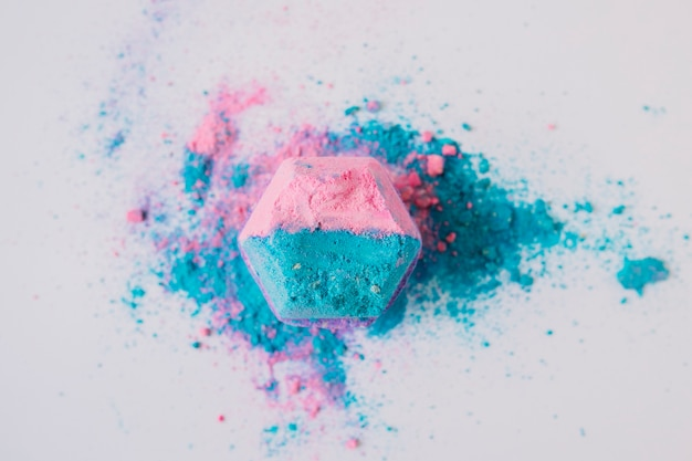 Opgeheven mening van roze en blauwe gekleurde badbom op witte achtergrond