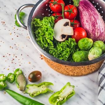 Opgeheven mening van ruwe gezonde groenten op marmeren achtergrond