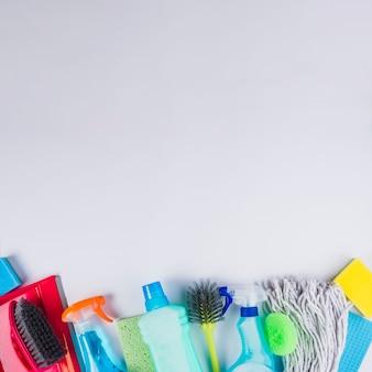 Opgeheven mening van schoonmakend materiaal bij de bodem van grijze achtergrond
