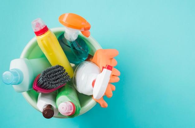 Opgeheven mening van schoonmakende producten in emmer op turkooise achtergrond