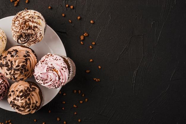 Opgeheven mening van smakelijke muffins op witte plaat