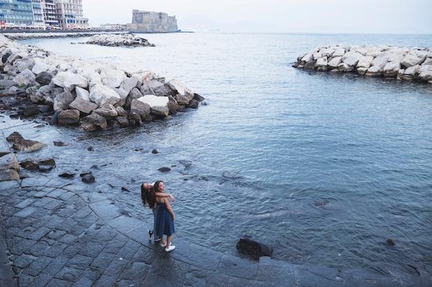 Opgeheven mening van twee vrouwelijke vrienden die zich dichtbij het overzees bevinden