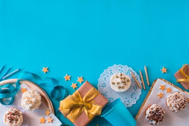 Opgeheven mening van verjaardagsgiften met muffins en kaarsen op blauwe oppervlakte