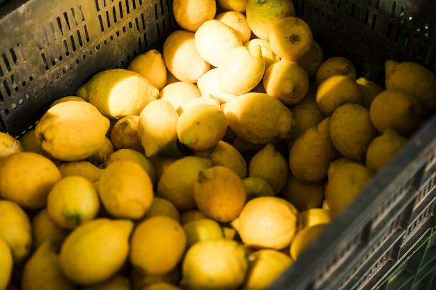 Opgeheven mening van verse sappige citroen in krat bij fruitmarkt