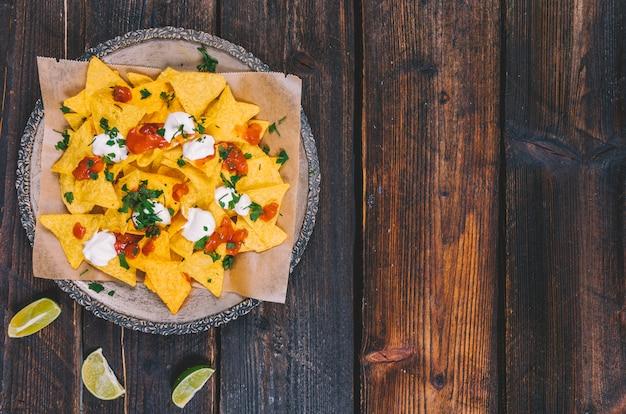 Opgeheven mening van versierde smakelijke mexicaanse nachos in plaat met citroenplakken op bruin houten bureau