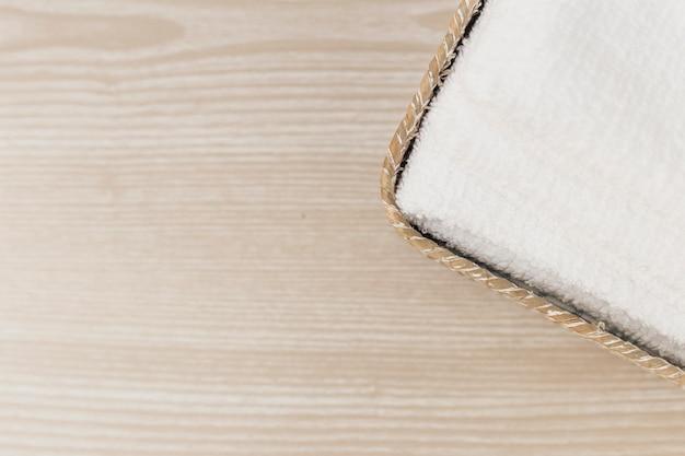 Opgeheven mening van witte handdoek in dienblad op houten achtergrond