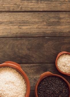 Opgeheven mening van witte kommen en zwarte rijstgraankommen op houten achtergrond