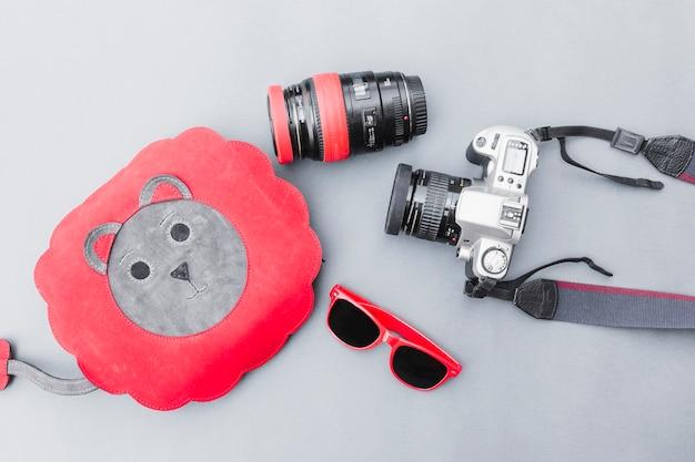Opgeheven mening van zak, zonnebril en dslr-camera op grijze achtergrond