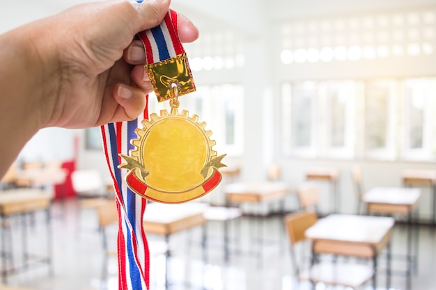 Opgeheven studentenhanden houdend twee gouden medailles met thais lint