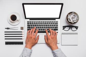 Opgeheven van de hand die van een persoon aan laptop in bureau werkt