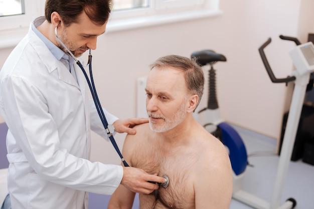 Opgeleide prominente jonge specialist die regelmatig onderzoek doet en zijn stethoscoop gebruikt terwijl hij zijn patiënt raadpleegt